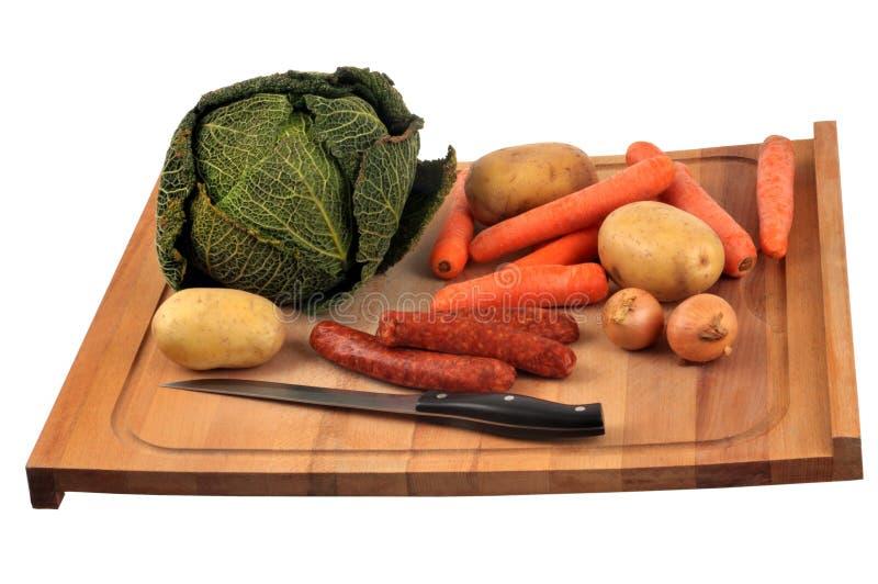 Warzywa i kiełbasa na tnącej desce na białym tle obrazy stock