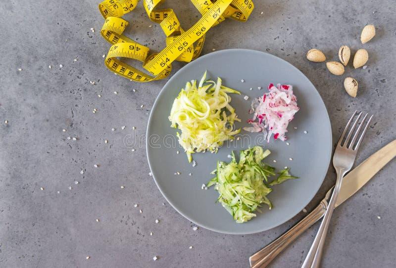 Warzywa na blacie, cucchini, rzodkiew, ogórek, widły, nóż na szaro, orzechy, centymetr obraz stock