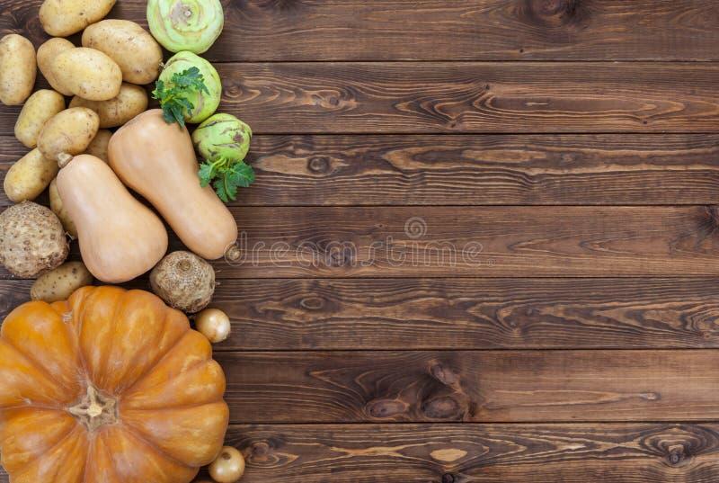Warzywa na drewnianym tle Bania, zucchini, grule, cebule i inni warzywa, odgórny widok, kopii przestrzeń obrazy royalty free