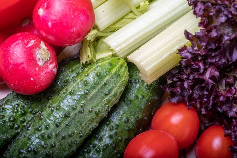 Warzywa na lekkim drewnianym stole, czerwonej papryce, selerze, liściach sałata, pomidorowej wiśni, ogórkach i rzodkwiach, obrazy stock