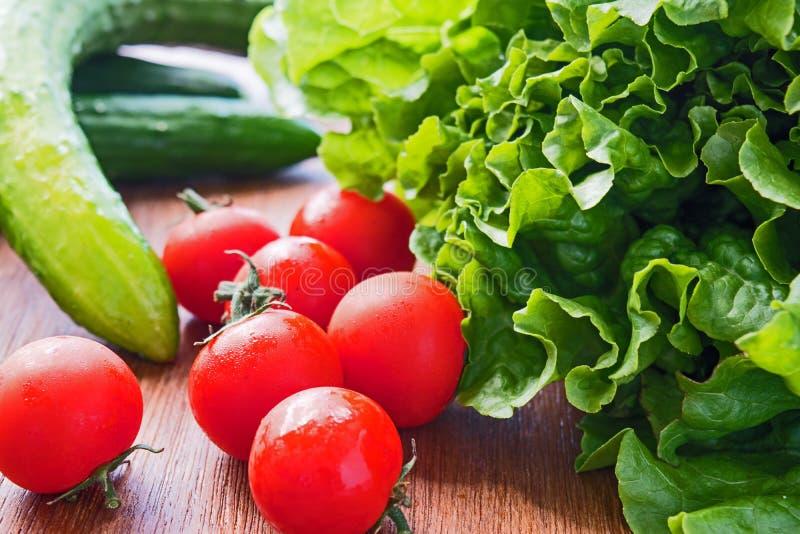 Warzywa Pomidor, ogórek, zielona sałatka drewniana zdjęcia royalty free