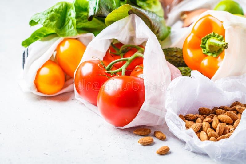 Warzywa w eco bawełnianych torbach, pieprzu, pomidorze, sałacie, ogórku, wapnie, cebuli i dokrętkach, Zero jałowy karmowy zakupy fotografia stock