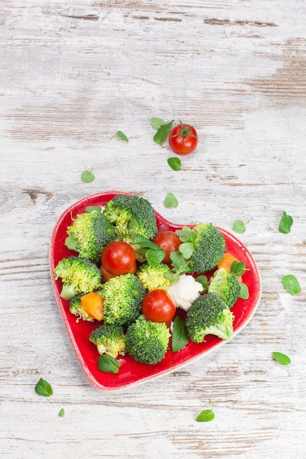 Warzywa w serce kształtującym talerzu zdjęcie stock