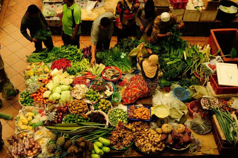 Warzywo i moczy rynek Muzułmańska kobieta sprzedaje świeżych warzywa przy Siti Khadijah rynku rynkiem w Kot Bharu Malezja zdjęcia royalty free