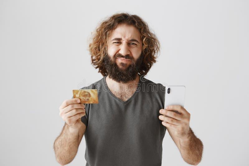 Was als Gesetzesbalance auf Bankkonto trauriger sein kann Atelieraufnahme des missfallenen düsteren Ostmannes mit Bart die Stirn  lizenzfreies stockfoto