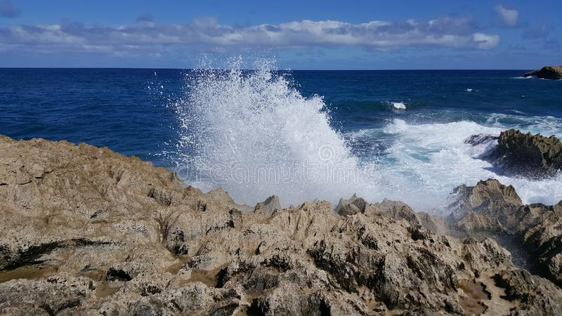 Was geschieht, wenn Welle Felsen trifft lizenzfreie stockbilder