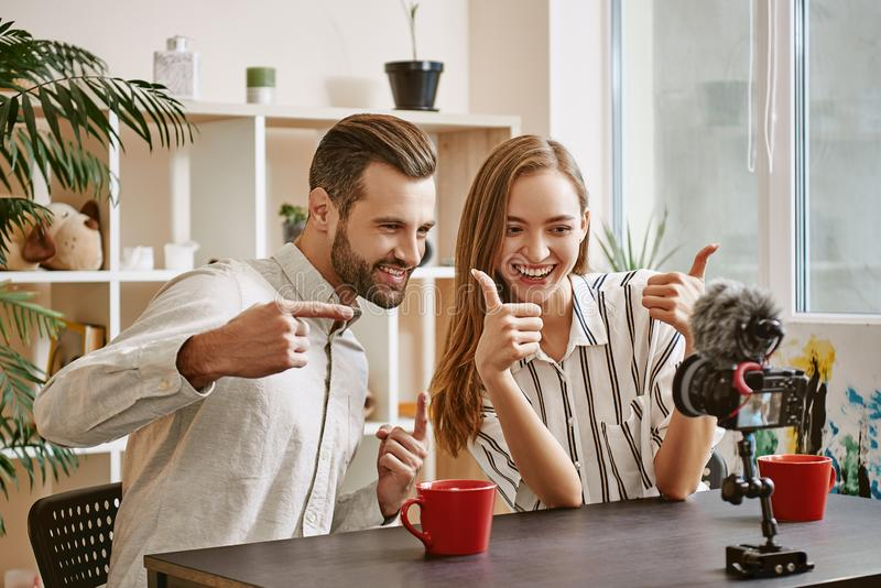 It was great streaming! Couple of positive bloggers are gesturing and smiling on tripod mounted digital camera. Couple. Social Media. Blog. Content royalty free stock photos