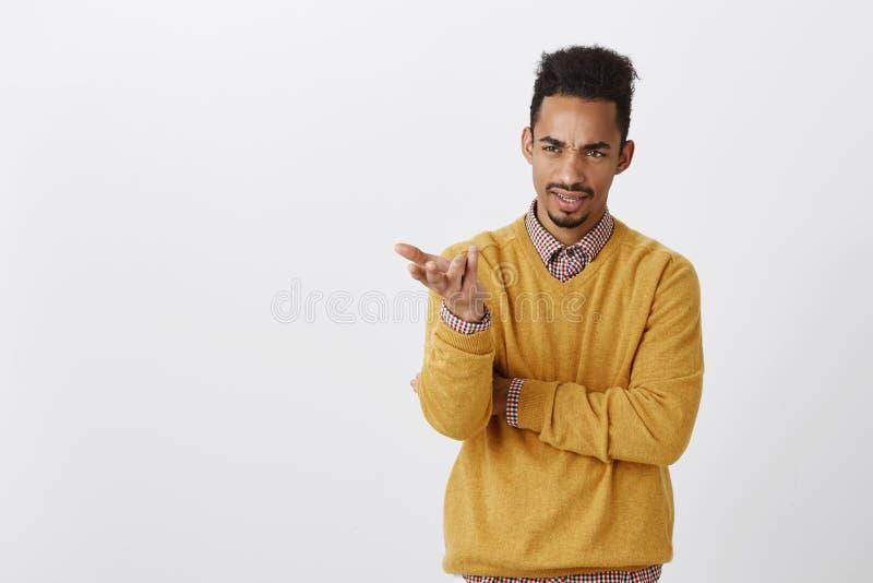 Was Ihr Punkt ist, Geck Porträt des missfallenen dunkelhäutigen männlichen Büroangestellten im gelben Pulloverhändchenhalten halb stockbilder