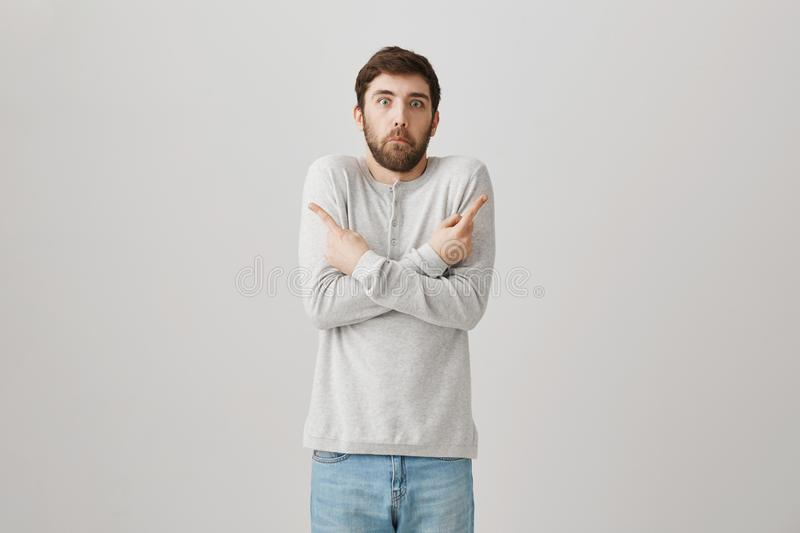It was not me ask someone else. Studio shot of clueless and confused man trying to hang blame on others, pointing in. Both ways with crossed hands and making royalty free stock photos