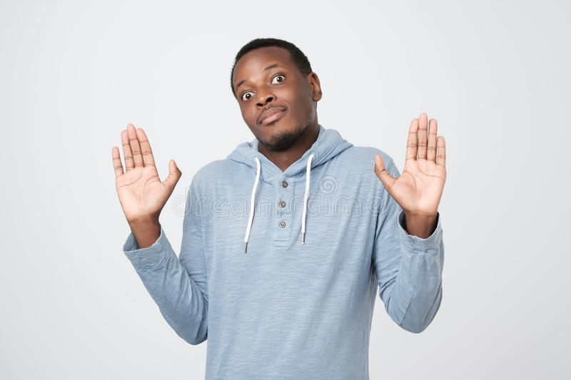 Confused african man raising palms in surrender, shrugging and making clueless expression stock photos