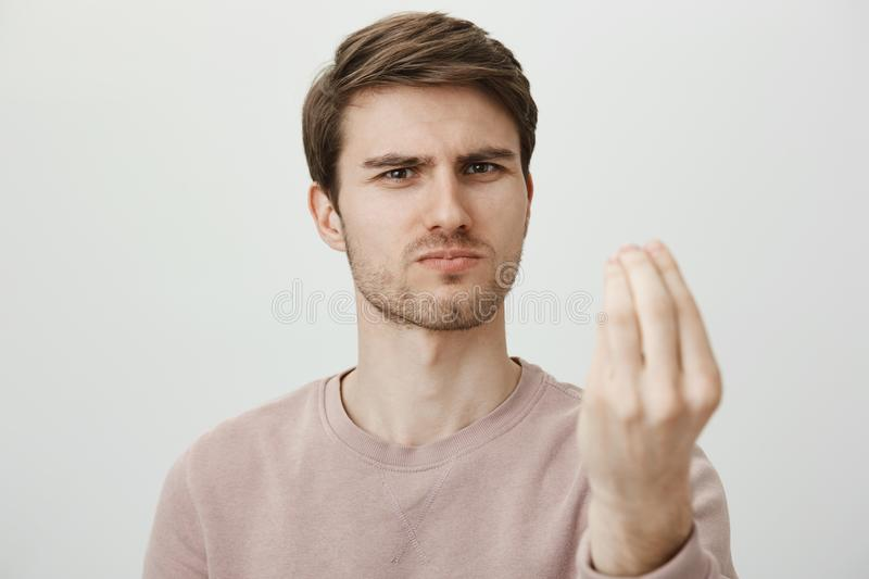 It was perfect show. Serious good-looking mature male squinting and frowning while making strict face of expert, showing. Italian gesture with fingers folded royalty free stock photo