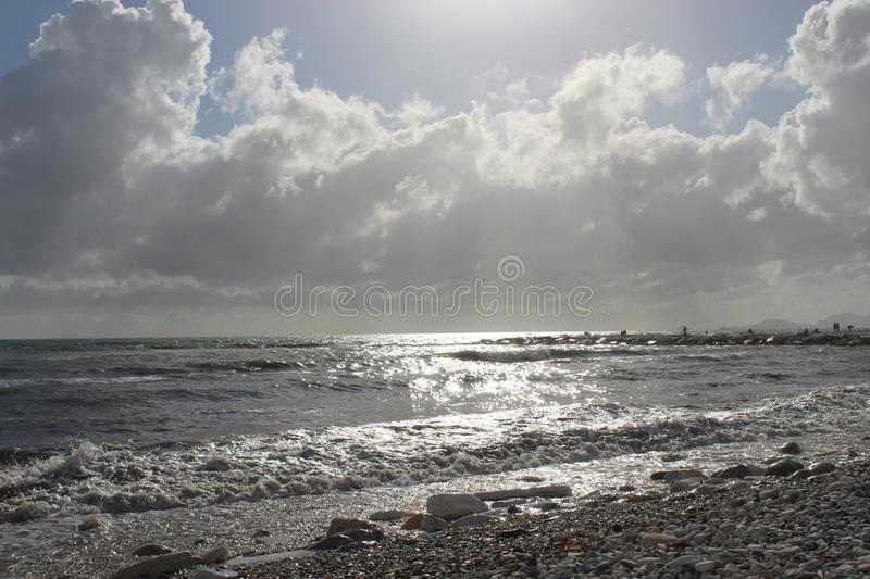 A nice afternoon at the beach in Tuscany, Italy. It was a sunny day at the beach. You could see the high  waves in the water.  There are rocks in the ocean royalty free stock images