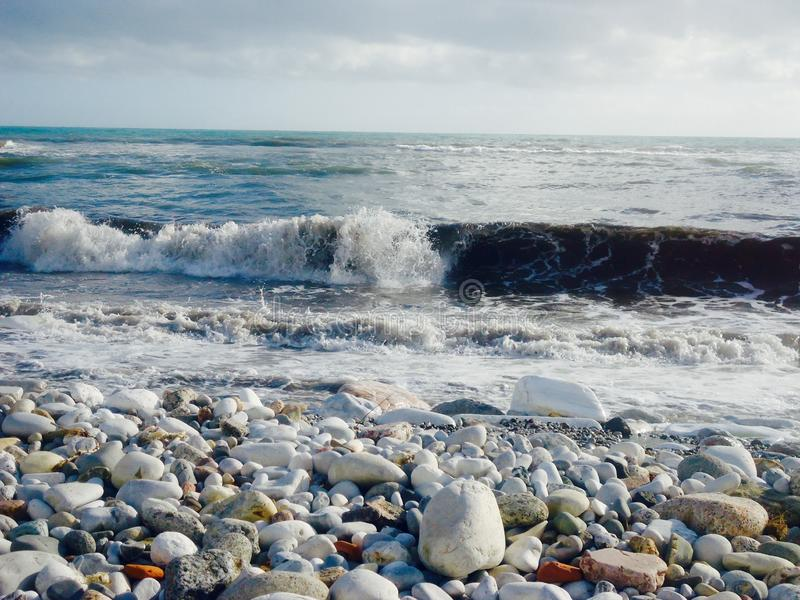 A nice afternoon at the beach in Tuscany, Italy. It was a sunny day at the beach. You could see the high  waves in the water.  There are rocks in the ocean stock photo