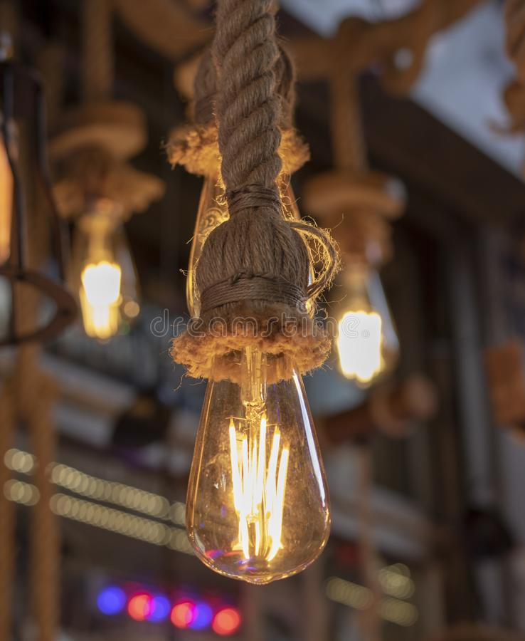 It was taken in front of the store. Lamps hanging on rope, brown rope and yellow light stock images