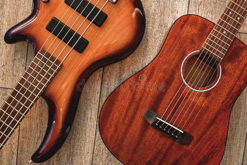 Was, zum von Draufsicht über zwei kühle Musikinstrumente zu wählen: akustisch und E-Gitarren liegen auf dem Bretterboden herein lizenzfreie stockfotografie