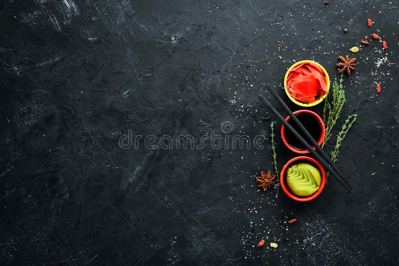 Wasabi, ginger and soy sauce. Top view. Free space for your text. On a black background royalty free stock photos