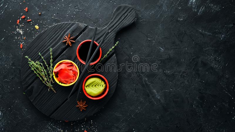Wasabi, ginger and soy sauce. Top view. Free space for your text. On a black background royalty free stock photography