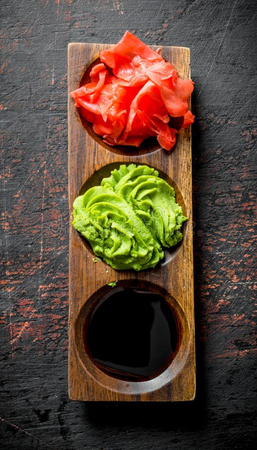 Wasabi, marinated ginger and soy sauce for Japanese sushi. On dark rustic background royalty free stock photography