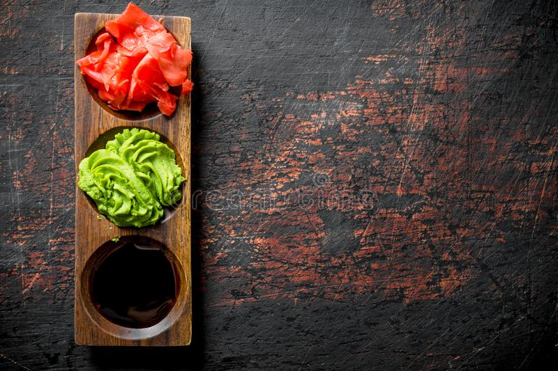 Wasabi, marinated ginger and soy sauce for Japanese sushi. On dark rustic background royalty free stock image