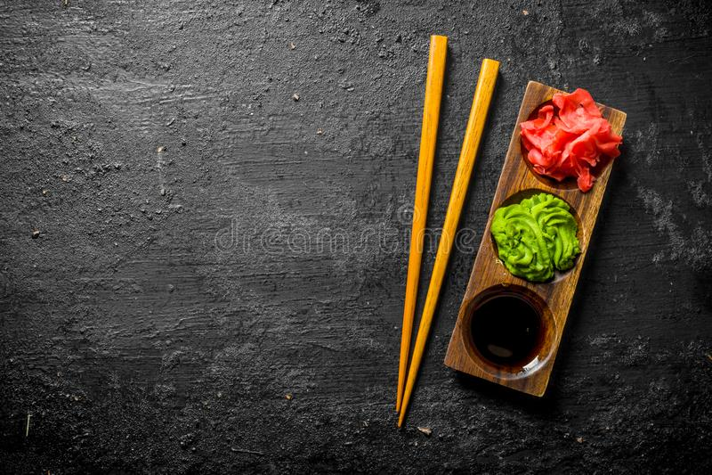 Wasabi, marinated ginger and soy sauce in a wooden stand with chopsticks. On black rustic background stock photo