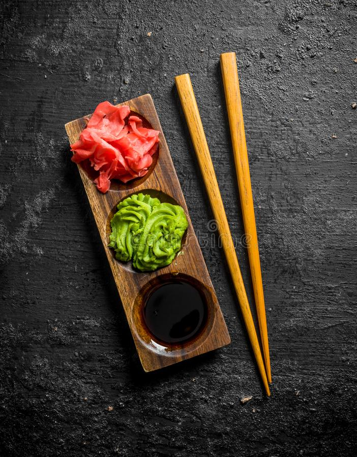 Wasabi, marinated ginger and soy sauce in a wooden stand with chopsticks. On black rustic background royalty free stock image