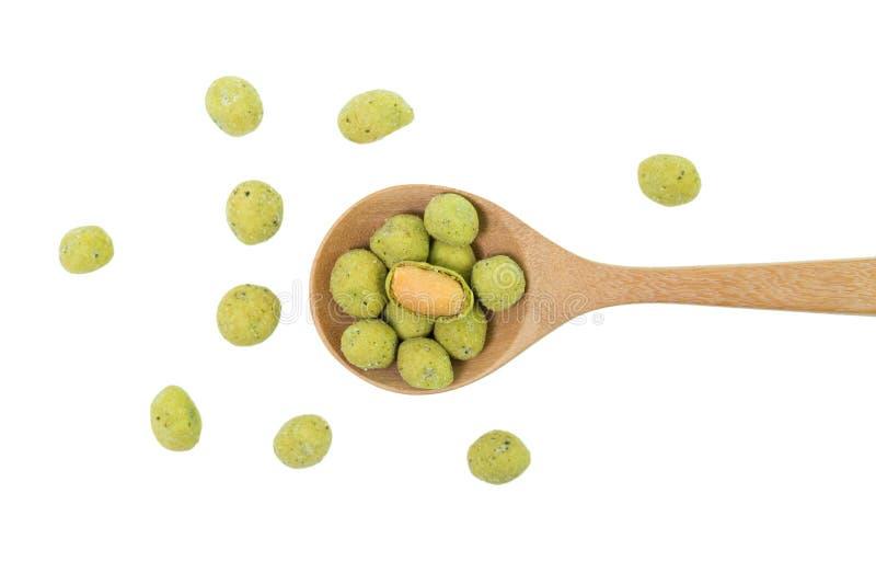 Wasabi przekąski crispy arachidowe piłki w drewnianej łyżce odizolowywającej na białym tle zdjęcia royalty free