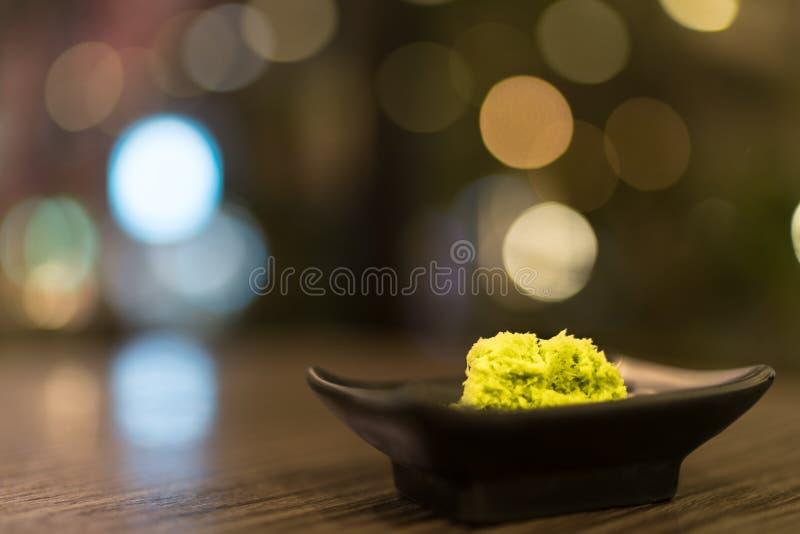 Wasabi w czarnym spodeczku na drewnianym stole z głębią śródpolny skutek, Japoński karmowy ` s condiment, bokeh tło zdjęcie royalty free