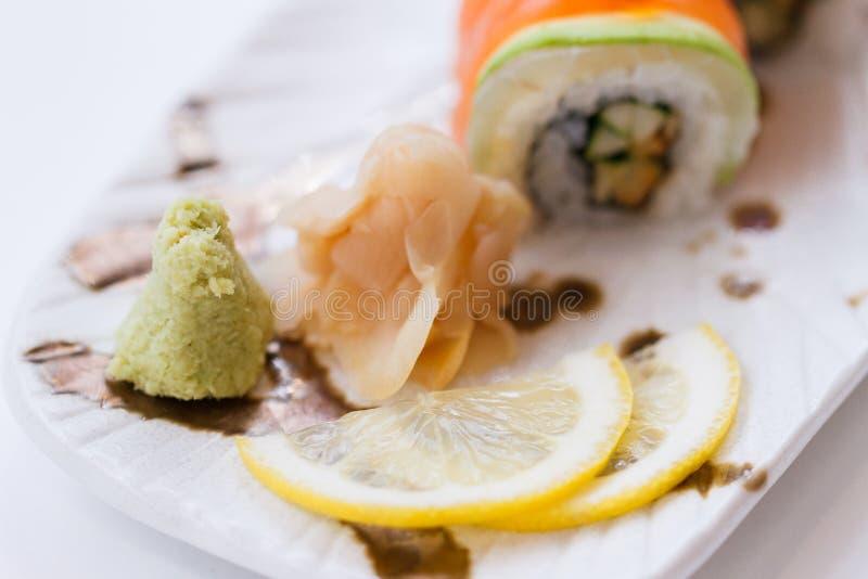 Wasabi, zenzero formicolato e limone affettato con Maki Roll che ha rotolato con il salmone, l'avocado e Maguro Tuna Topping con  fotografia stock libera da diritti