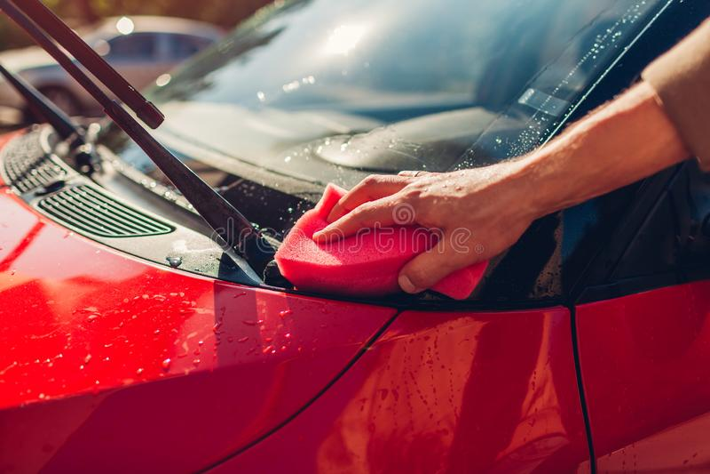 Wasauto's Man die auto schoonmaakt met een zeepspons in de openlucht Sluiten royalty-vrije stock foto's