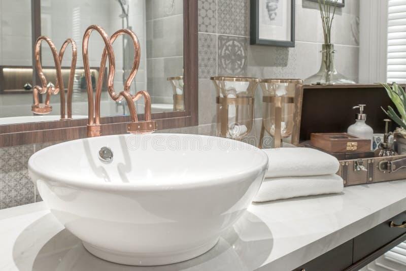 Wasbak met handdoek en decoratie in badkamers stock foto