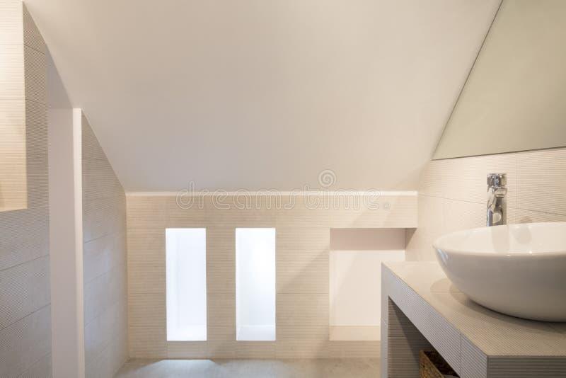 Waschbecken im hellen minimalen Badezimmerinnenraum im Dachboden mit stockbilder