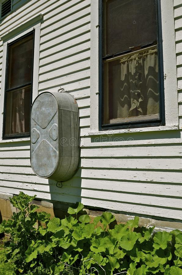 Waschbottich, der an der Bauernhauswand hängt stockbild