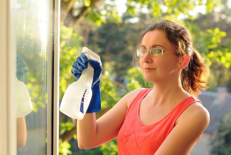 Waschende Fenster der jungen Frau Schöne junge Hausfrau, die Hausaufgaben tut lizenzfreie stockbilder