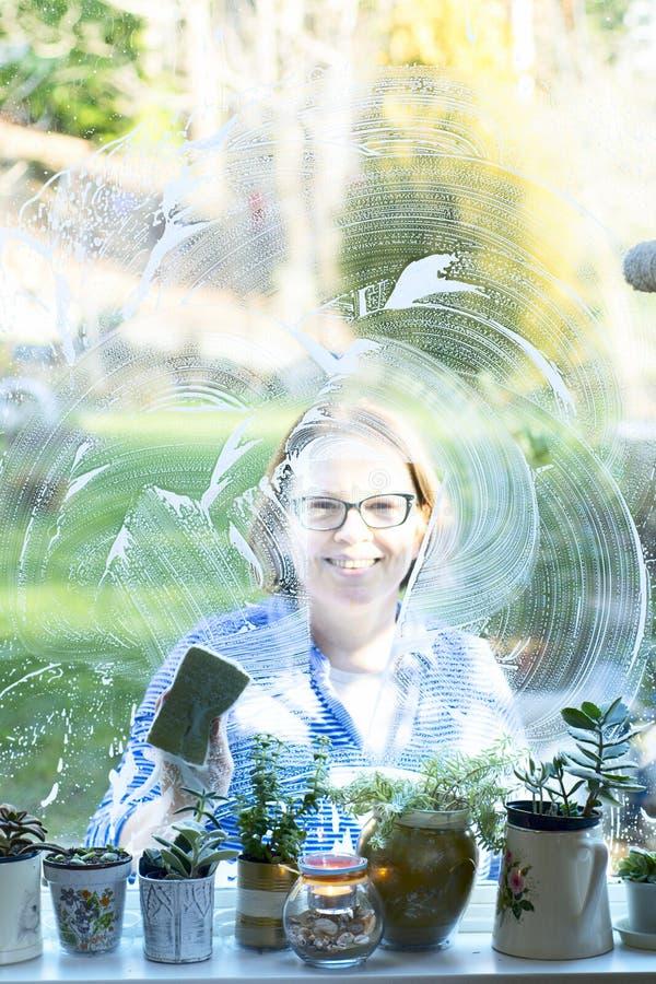 Waschende Fenster einer Frau lizenzfreies stockbild