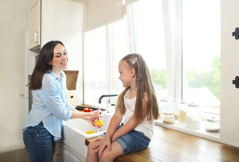Waschende Früchte der Mutter und der Tochter an der Küche lizenzfreies stockbild