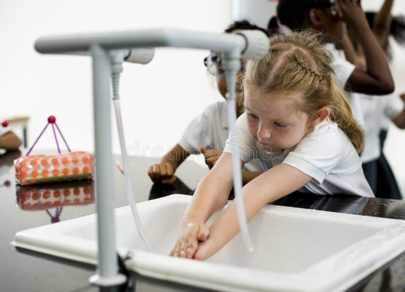 Waschende Hände des jungen Mädchens mit Wasser lizenzfreies stockfoto