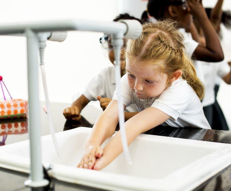 Waschende Hände des jungen Mädchens mit Wasser lizenzfreie stockbilder
