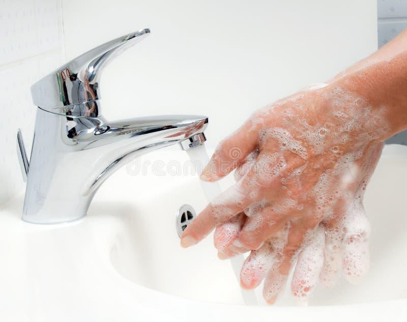 Waschende Hände mit Seife und Wasser lizenzfreie stockfotos