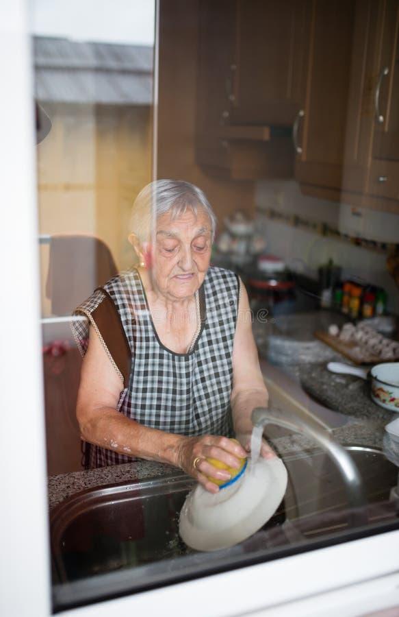 Waschende Teller der älteren Frau stockfotos