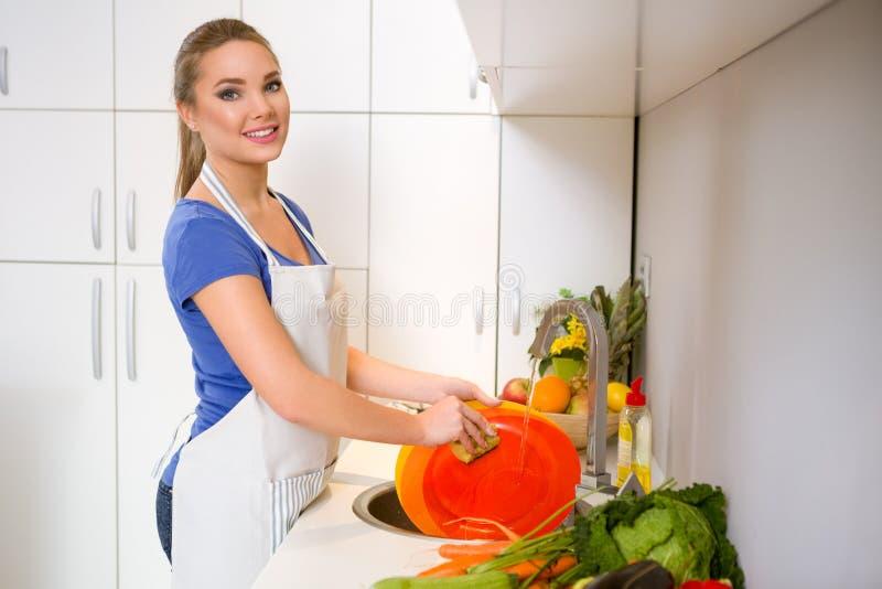 Waschende Teller der jungen Frau stockfotografie