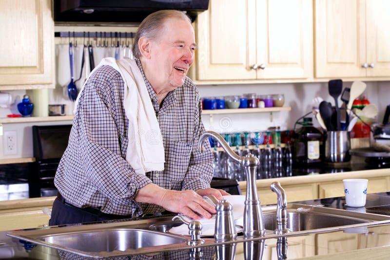 Waschende Teller des älteren Mannes stockfotos