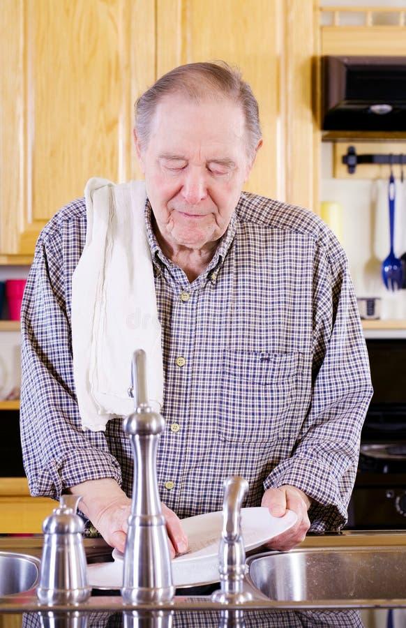 Waschende Teller des älteren Mannes lizenzfreies stockfoto