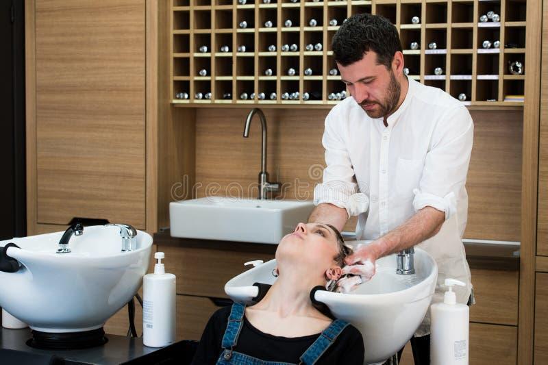 Waschender Kopf des Herrenfriseurs zur jungen Frau am Friseur stockfotos