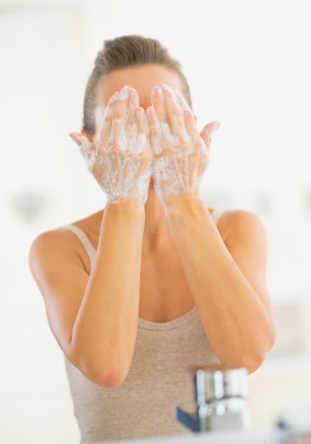 Waschendes Gesicht der jungen Frau im Badezimmer lizenzfreies stockfoto