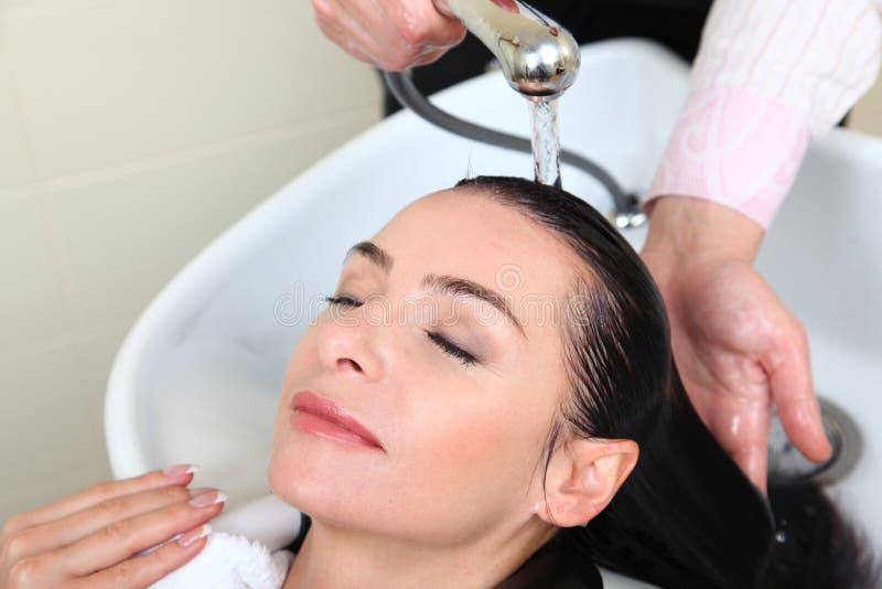 Waschendes Haar der Frau im Salonpool lizenzfreie stockfotografie