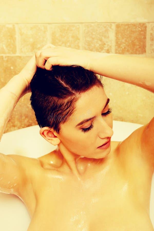 Waschendes Haar der jungen schulterfreien Frau im Bad lizenzfreie stockbilder
