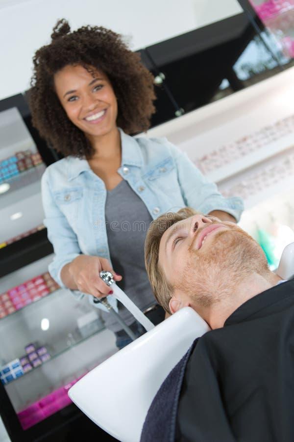 Waschendes Haar des glücklichen Friseurs zum Kunden vor dem Handeln von Frisur lizenzfreies stockfoto