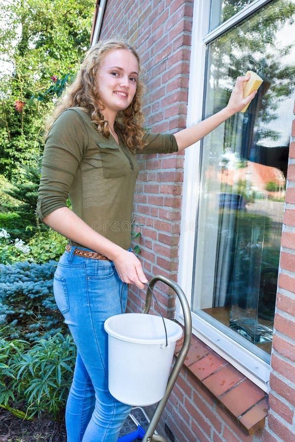 Waschendes Hausfenster der jungen niederländischen Frau draußen stockfoto