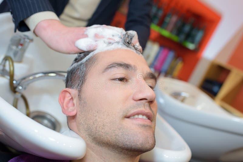 Waschendes männliches Haar des Friseurs mit Konzentration lizenzfreie stockbilder
