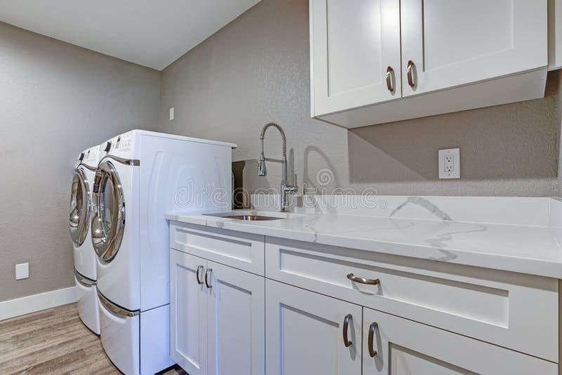 Waschküche mit Taupewänden und Marmorplattekabinetten stockfotografie
